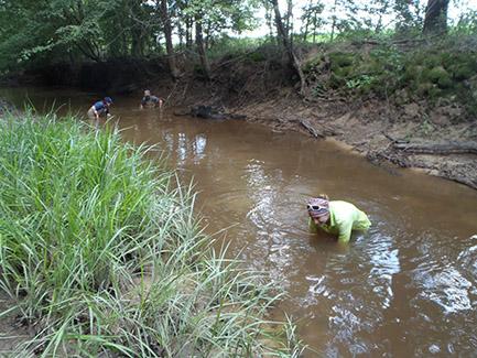 team in a creek taking water samples