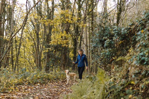 A women and her dog hiking on a trail