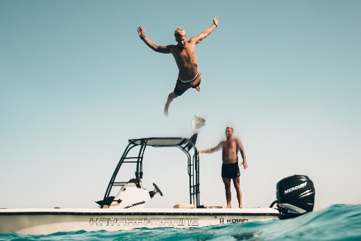 Man jumping off of a boat