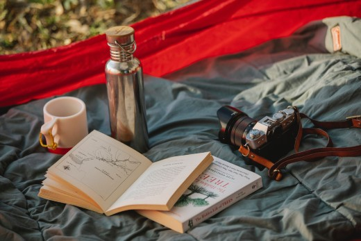 nature guide and coffee mug inside a tent