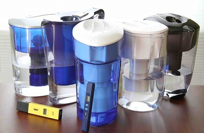 Five large handheld water filter dispensers on a table
