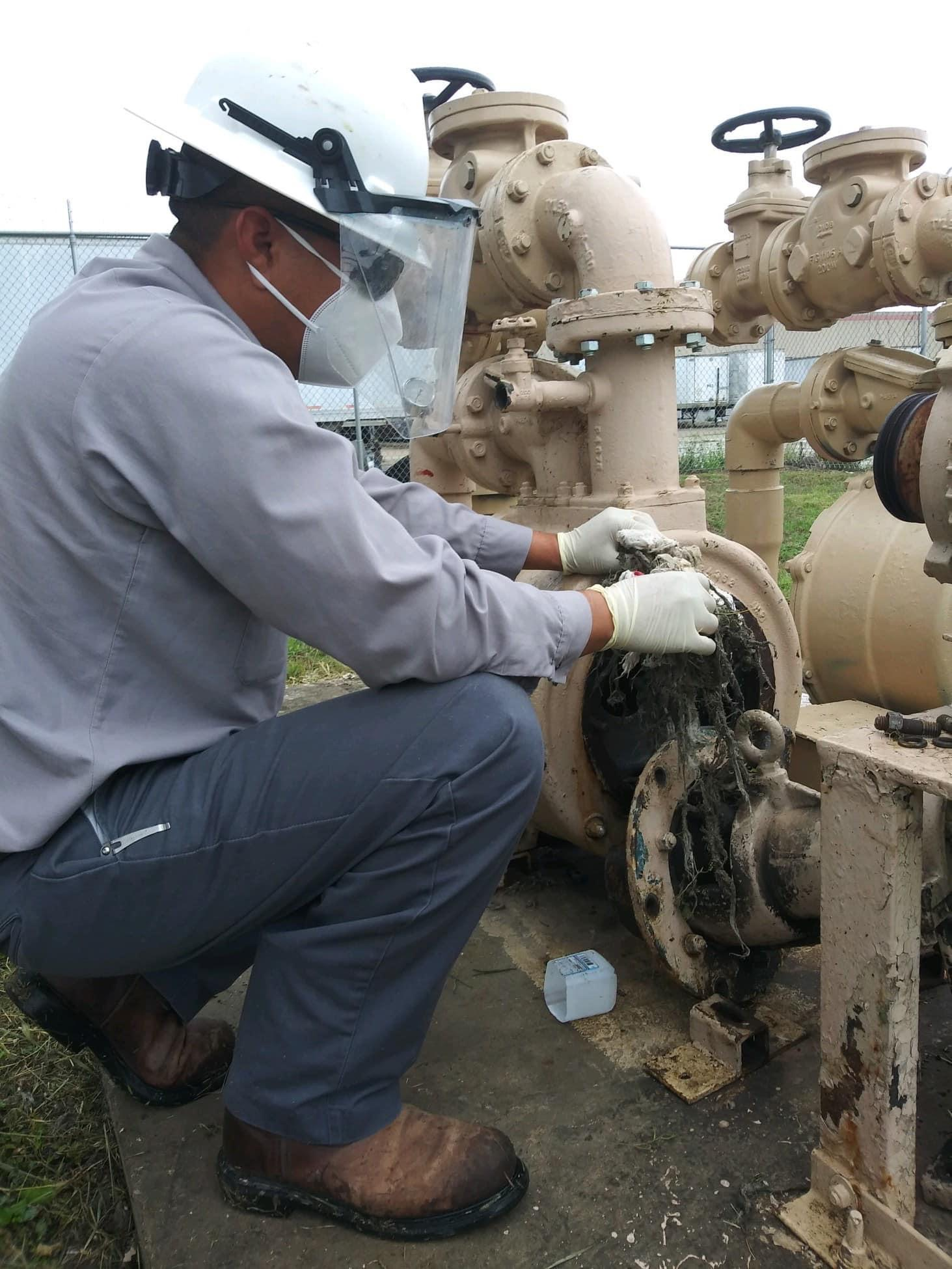 maintenance worker clearing clogged pipe