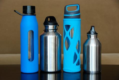 Four metal and glass reusable water bottles on a table