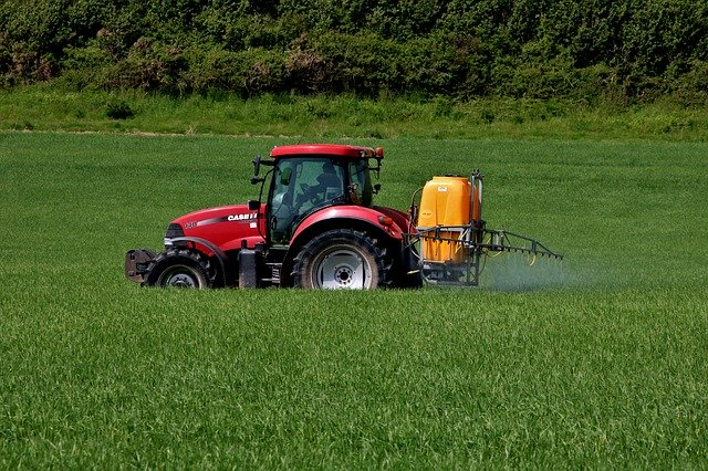 Red tractor spraying insecticide on crops