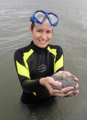 Sarah in a wetsuit, hip deep in water, holding a mud sample