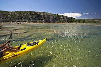 Kayaker paddling across clear water near shoreline