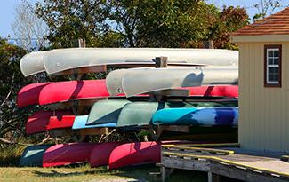 Canoes stored upsidedown in outdoor racks beside building