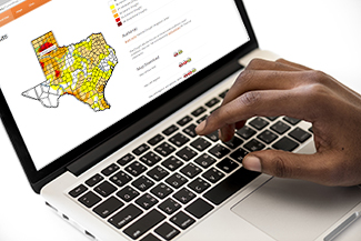 hand on keyboard searching for drought areas in Texas