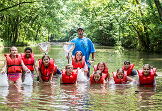 4-H Water Investigator Program students posed in creek wearing life jackets