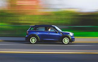 blue mini cooper racing down street