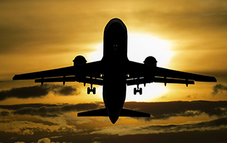 silhouette of airplane lifting off in front of sun