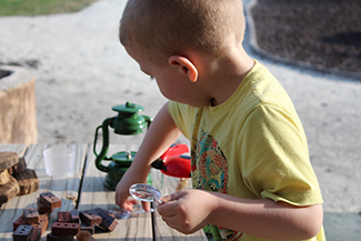 little boy playing with pieces on wooden table