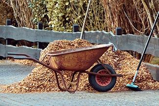 wheelbarrow full of wooden mulch chips