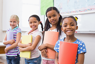 young girls holding folders in front of whiteboard