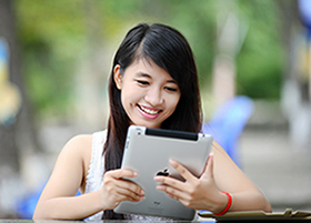 woman smiling at ipad in hands