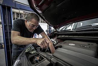 mechanic maintaining vehicle engine