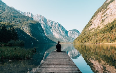 person sitting on pier overlooking lake among mountains